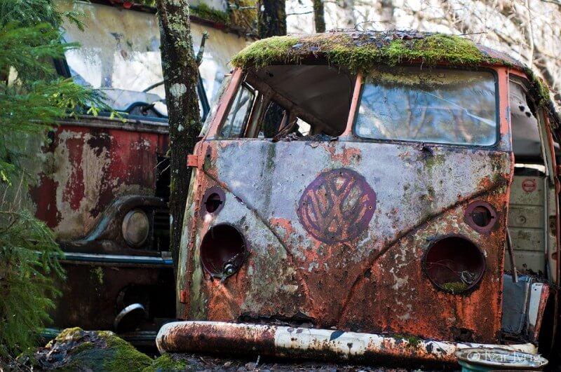 Nedrustet bil med en nedrustet lastebil i bakgrunnen